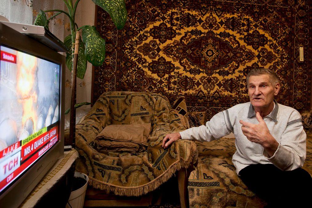 Kiew, Ukraine, 2011. Victor Gaydak, 70, einer der Liquidatoren, verfolgt im Fernsehen die Ereignisse im japanischen Fukushima.