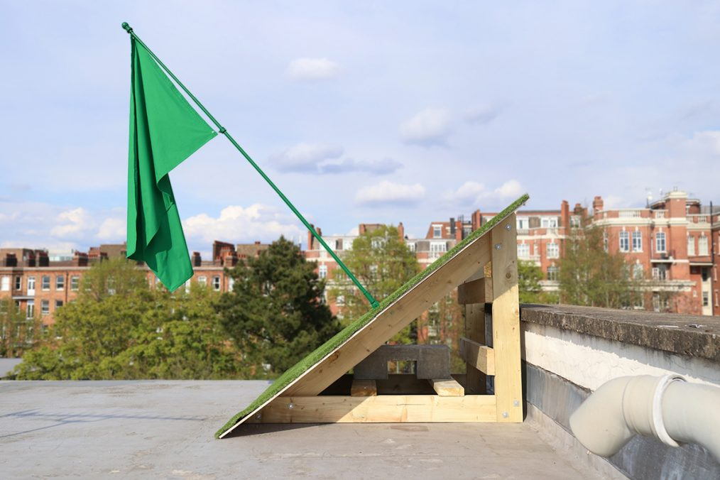 Allegory. Flag, flag pole, artificial grass, wooden structure 2021