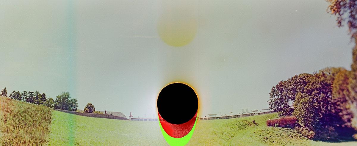 """Die Ansicht, 2017 Analoge Panoramafotografie, Lambda-Print, 56 × 140 cm  Ort: Ansicht von Mauthausen Richtung Südwesten aus der Ferne Technik: Die Negative wurde vor Belichtung mehrfach gekocht, gelocht und dann gefaltet. Konzept: Der Titel """"Ansicht""""  ist doppeldeutig: Einerseits sieht man Mauthausen von einem Hochsitz aus, andererseits starrt einen ein schwarzer Fleck an. Handelt es sich hierbei um die Historie, die uns mit ihrer Pupille im Blick hat, oder verhält es sich umgekehrt: Ist es der Betrachter, der den blinden Fleck der Historie erst erkennt? © Courtesy of the Artist & Galerie Michaela Stock"""