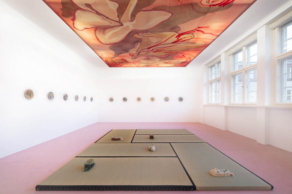 Installation view: Matthew Lutz-Kinoy. Window to The Clouds; Salon Berlin, Museum Frieder Burda Matthew Lutz-Kinoy, Wings of Flamingos, Camargue, 2020. Acrylic on canvas, 380 × 690 cm. Courtesy of the artist; Keramikos 3, 2019. Hand-painted set of 20 glazed ceramic plates. Courtesy of the artist and Mendes Wood DM São Paulo, New York and Brussels; Pillow In Cognac With Relaxed Figure, 2018; Pillow In The Form Of Reclining Child With Polkadots, 2018; Pillow In Green With Relaxing Figure, 2018; Pillow In The Form Of Reclining Child With Landscape, 2018; Pillow In The Form Of Reclining Child, Fishing Net, 2018. Glazed ceramics, dimensions variable. Courtesy of the artist and Fitzpatrick Gallery; Photo: Thomas Bruns